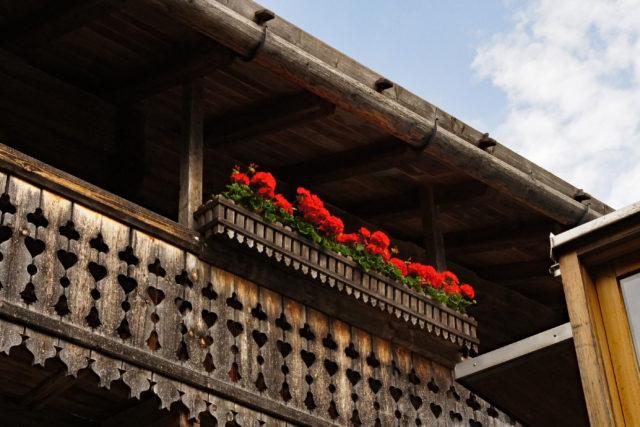 Balkon des Rablhauses mit roten Geranien, im Eck ist noch der moderne Zubau sichtbar