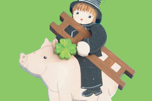 Schwein, auf dem ein Kaminkehrer mit Leiter sitzt, der einen grünen Vierklee in der Hand hält