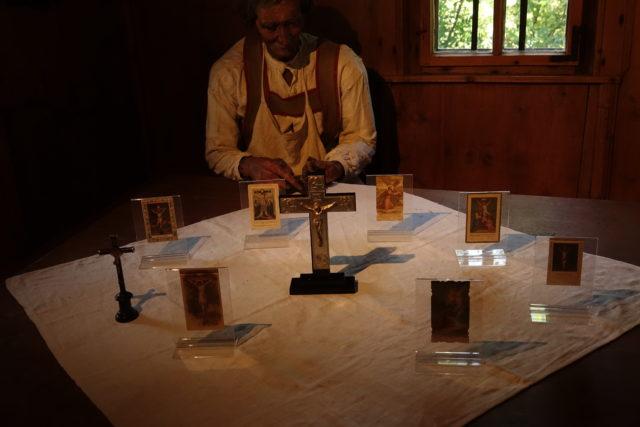 Kruzifixe und Andachtsbildchen mit Kreuzdarstellungen, präsentiert auf dem Tisch in der Stube des Rablhauses