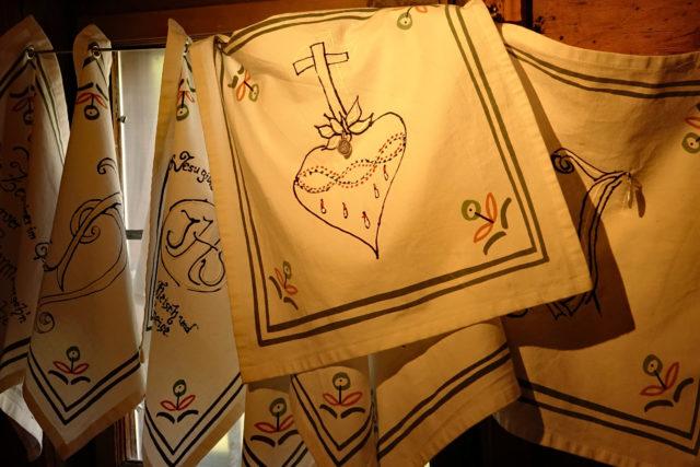 Textildrucke religiöser Symbole und Sprüche in Kombination mit religiösen Elementen (Medaillen) der Innsbrucker Künstlerin Sabine Schennach