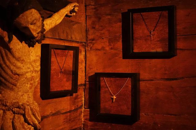 Schmuckkreationen in Kreuzform der Innsbrucker Künstlerin Claudia Gold neben einem Kruzifix