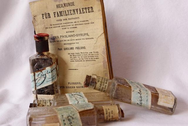 historische Medizinfläschchen mit Anleitungsbuch
