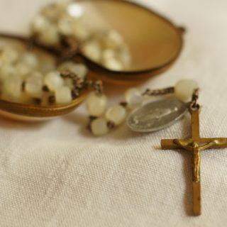 Rosenkranz mit Messingkreuz, im Hintergrund Perlmuttdose