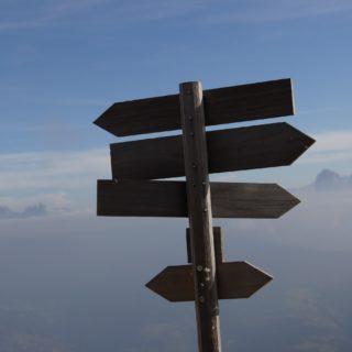 Wegweiser aus Holz mit einer Bergkette (Dolomiten) im Hintergrund
